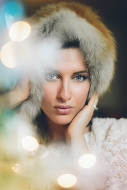 An image of a female model with blurred foreground lights - what is aperture