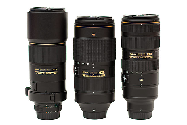 Three DSLR telephoto lenses side by side - the Nikon 300mm f/4D, Nikon 80-400mm, and Nikon 70-200mm