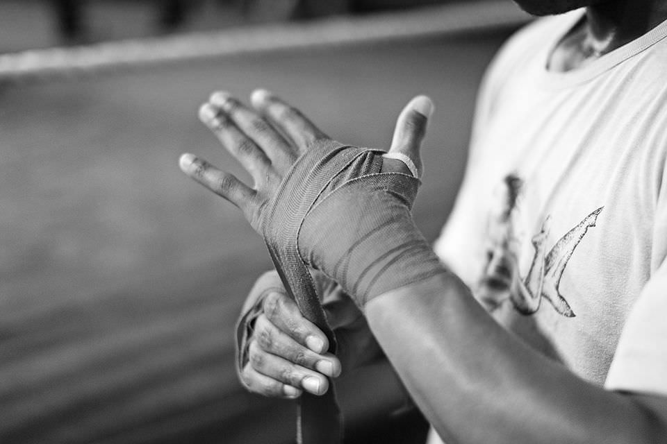 One of the young boxers prepares for the training session by putting bandages on his hands. They keep the hands and joints warm and less breakable.