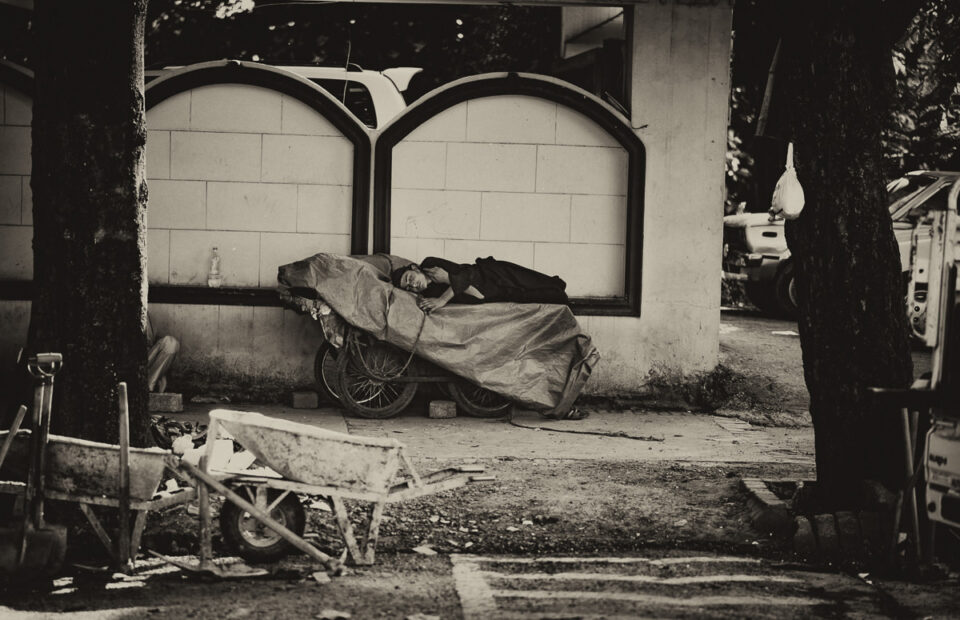 Caption: A young laborer takes a break from the day's work, napping on a cart parked outside the walls of a mansion.  The rear end of an SUV parked inside is a barely visible reminder of the stark income inequality that plagues that part of the world.