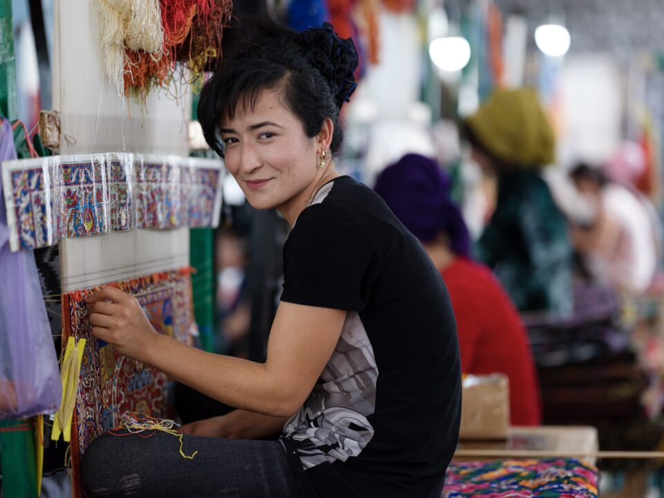Uzbek woman working on a silk carpet