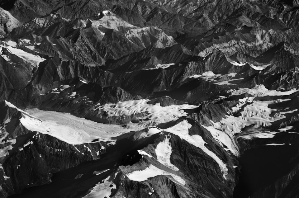 Black and white image of mountains with snow shot from distance