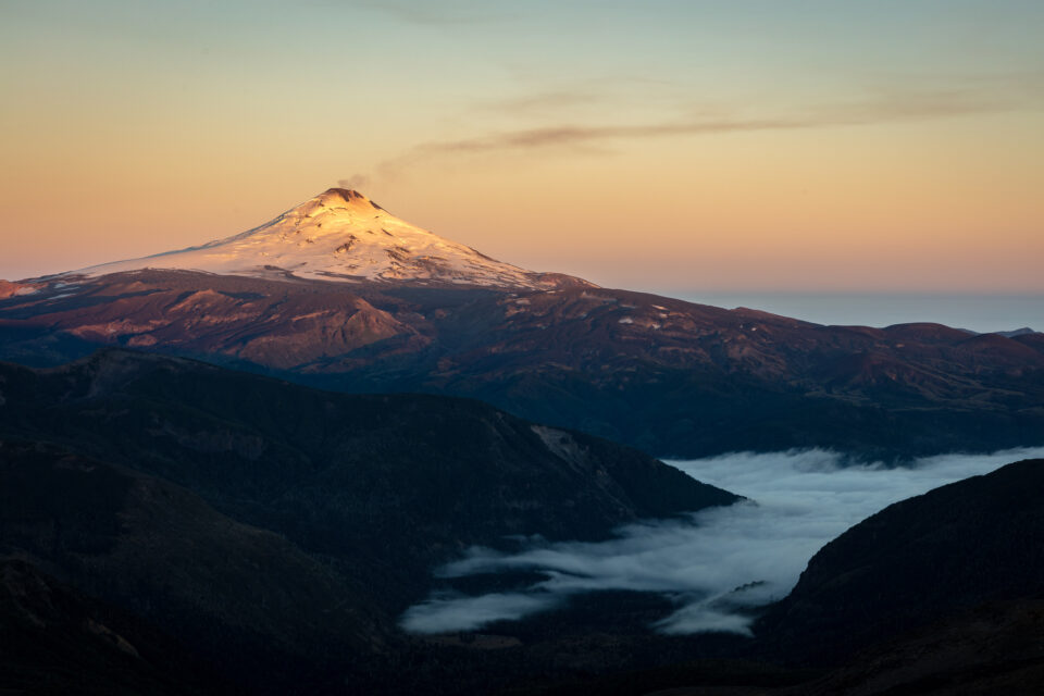 The Volcan Villarica Volcano is visible from a nearby mountain at sunrise, with thin plumes of smoke rising into the sky.