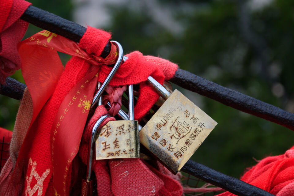 This sample photo from the Nikon D3500 shows a lock and red ribbons on a fence in China, specifically Huashan mountain.