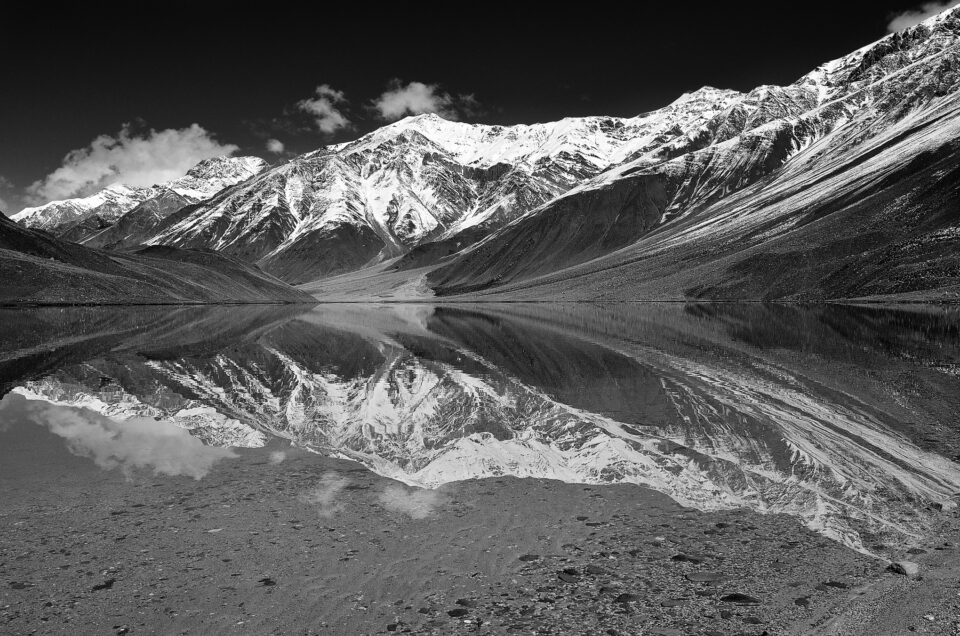 A black and white reflection shot of mountains with snow