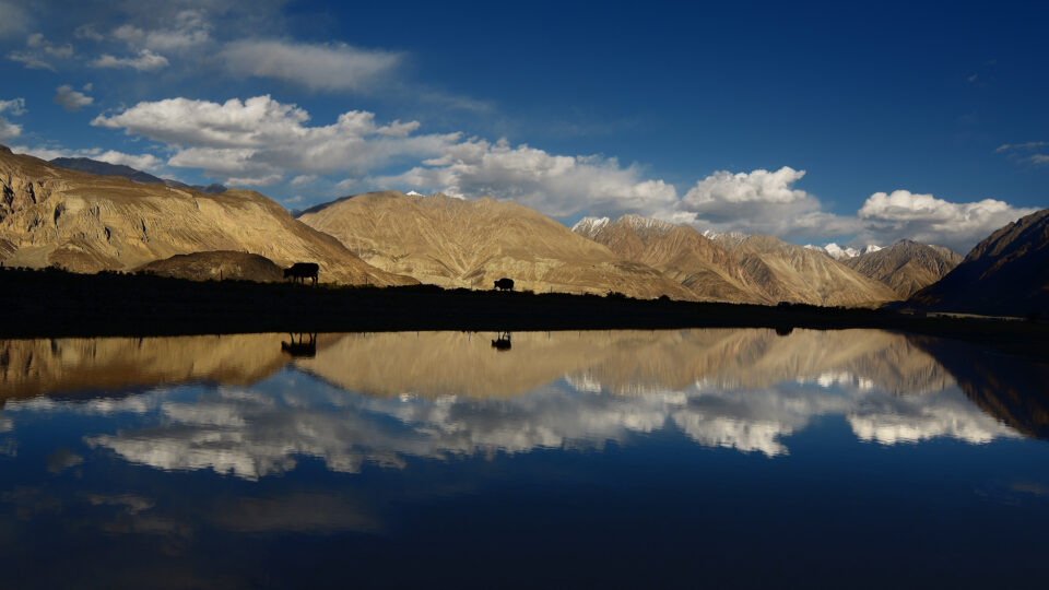 A dark lake reflection with mountains in the background