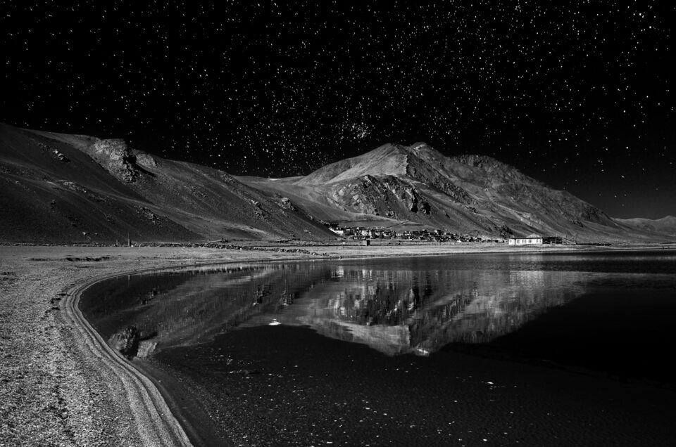 A lake reflection at night with mountains and stars
