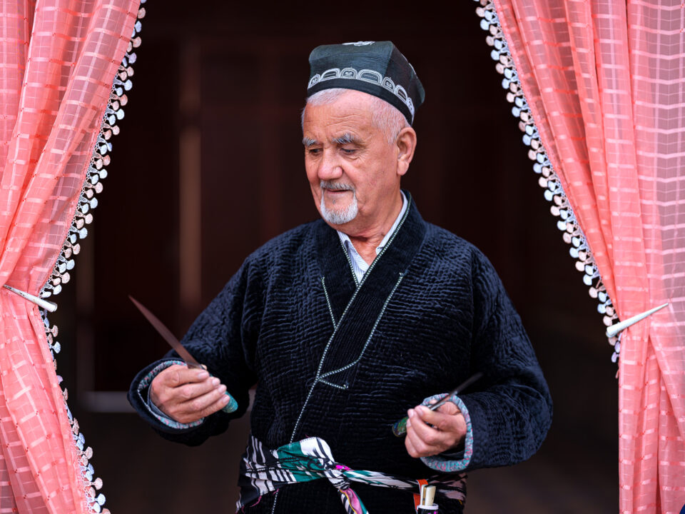 A master blacksmith from Andijan, Uzbekistan, holding a knife he made