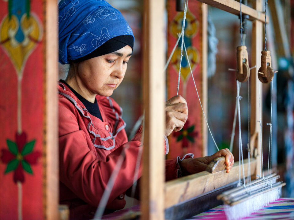 An image of a woman working on a silk loom, Uzbekistan