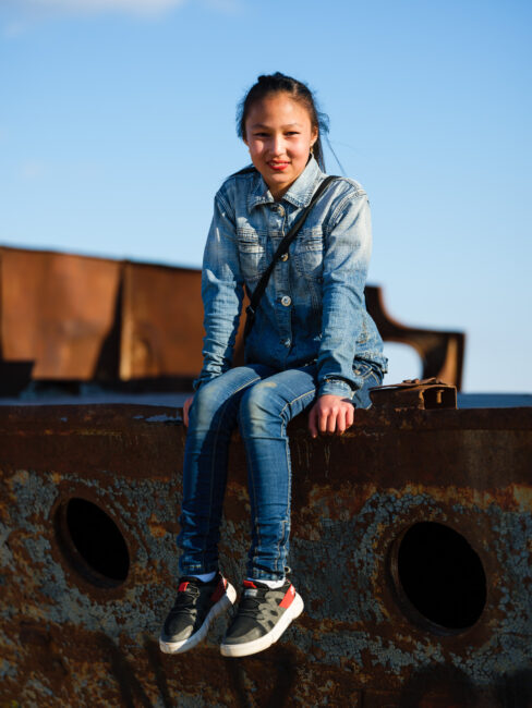 Local girl climbing a ship in the ship graveyard in Muynak